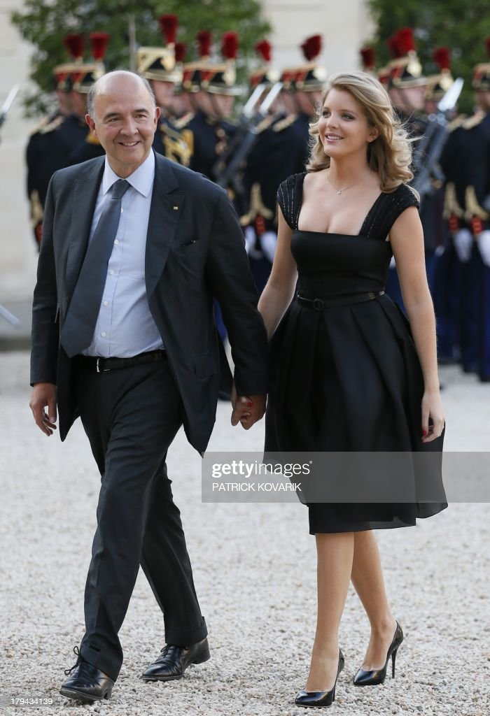 French Finance Minister Pierre Moscovici (L) and his companion Marie-Charline Pacquot arrive at the Elysee presidential palace, in Paris, on September,3 2013, for a State dinner with the French and the German presidents.