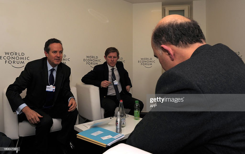 French Finance Minister Pierre Moscovici (R) listens to Standard and Poor's President Douglas Peterson (L) on January 25 during a meeting at the World Economic Forum (WEF) in the Swiss resort of Davos. The WEF will see top politicians and business leaders pursue talks on whether they have seen the back of the global financial crisis.
