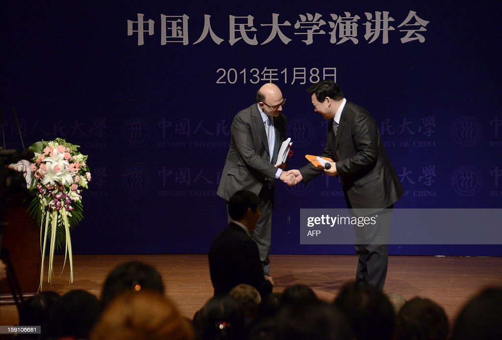 French finance minister Pierre Moscovici (L) shakes hands with Chen Yulu (R), headmaster of Renmin University, after giving a speech to students in Beijing on January 8, 2013. Moscovici began his two day visit to China on January 7.