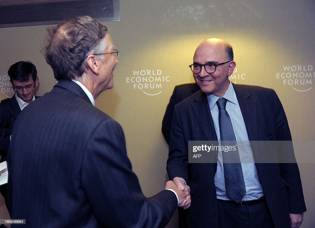 French Finance Minister Pierre Moscovici shakes hands with Microsoft founder Bill Gates at the World Economic Forum in Davos on January 25, 2013. The meeting gathers some of the world's leading politicians and economists and is viewed as a global think tank forum.