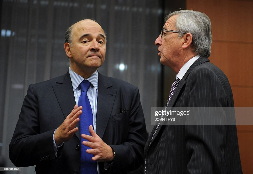French Finance minister Pierre Moscovici (L) speaks with Luxembourg Prime Minister and Eurogroup Council president Jean-Claude Juncker (R) before an Eurozone finance ministers meeting to decide on a fresh rescue loan for debt-stricken Greece, on November 20, 2012 at EU headquarters in Brussels. Greece has 'delivered' on reform and a deal will likely be clinched to unblock funds to keep it from bankruptcy, the head of the Eurogroup insisted despite a split with the IMF over how to get the stricken country's economic recovery on track.
