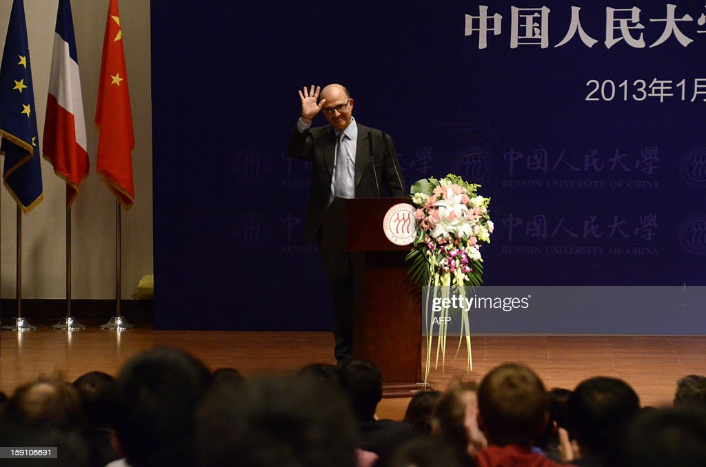 French finance minister Pierre Moscovici waves to students after delivering a speech at Renmin University in Beijing on January 8, 2013. Moscovici began his two day visit to China on January 7.