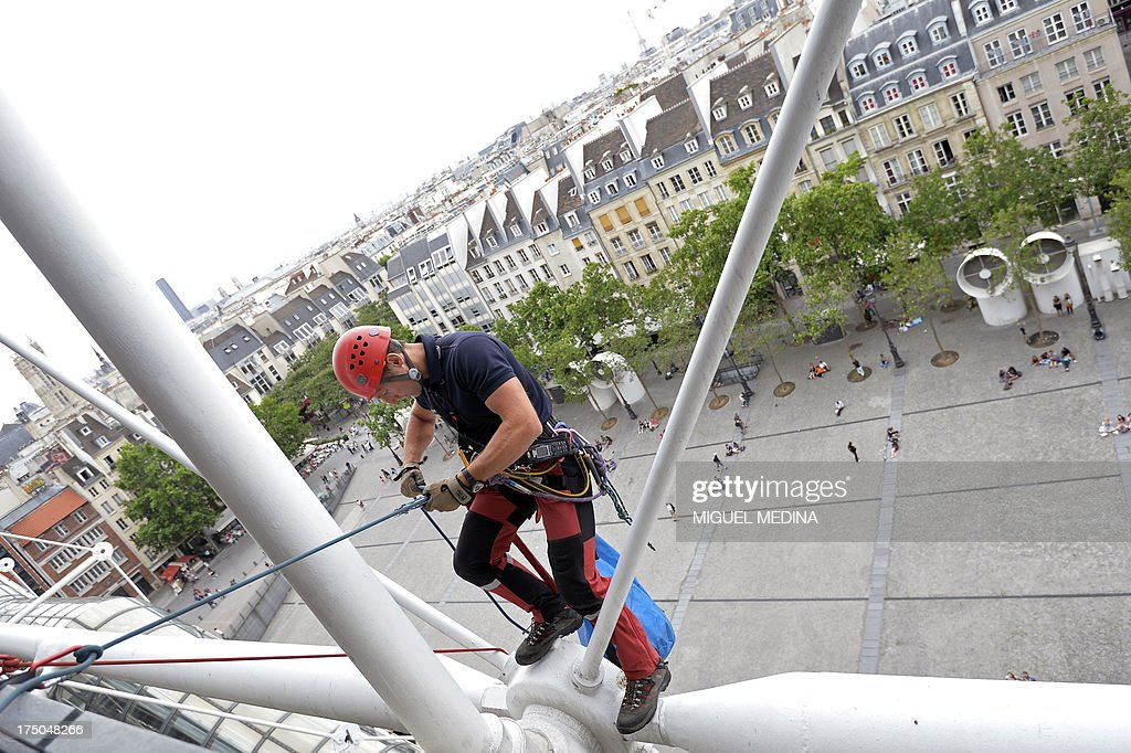A French firefighter from the GRIMP unit, specialized in vertical rescue operations, prepares climbing during a drill on July 30, 2013 at the Centre Pompidou, contemporary art center, aka Beaubourg, in Paris.