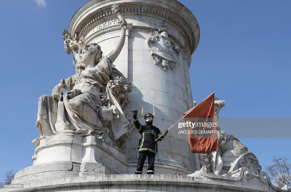 A French firefighter holds a Che Gevara flag during a protest of firemen against staff reduction on the place de la Republique in Paris on March 14, 2017. / AFP PHOTO / Jacques DEMARTHON