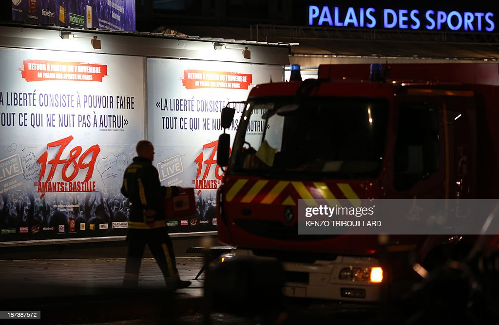 A French firefighter walks past an advertisement for the musical '1789, The Lovers of Bastille' outside the Palace of Sports at the Porte de Versailles in Paris following a blast on November 8, 2013. At least seven people were injured when an accidental explosion took place during a rehearsal of the play. AFP PHOTO/KENZO TRIBOUILLARD