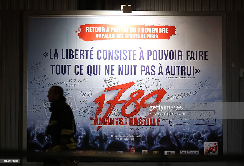 A French firefighter walks past an advertisement for the musical '1789, The Lovers of Bastille' outside the Palace of Sports at the Porte de Versailles in Paris following a blast on November 8, 2013. At least seven people were injured when an accidental explosion took place during a rehearsal of the play.