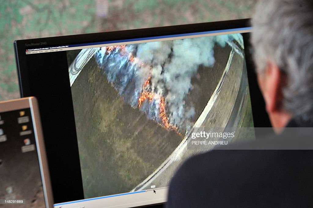 A French firefighter watches on a laptop aerial images showing a forest fire shot from an Unmanned Aerial Vehicle (UAV) (aka drone) of French Fly-n-Sense (FNS) company, on July 12, 2012 near Mont-de-Marsan, southwestern France, during tests in the Landes forest region as an innovative forest surveillance system which will enable a real-time monitoring of fire outbreaks and the development of flames in French southwestern forests.