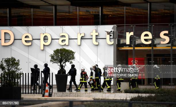 TOPSHOT French firefighters and RAID police unit officers secure Paris' Orly airport on March 18 2017 following the shooting of a man by French...