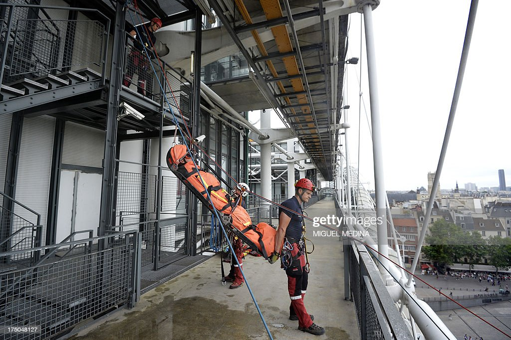 French firefighters from the GRIMP unit, specialized in vertical rescue operations, evacuate an injured as they stage a drill on July 30, 2013 at the Centre Pompidou, contemporary art center, aka Beaubourg, in Paris.