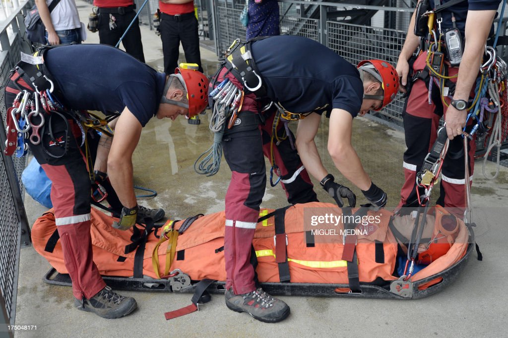 French firefighters from the GRIMP unit, specialized in vertical rescue operations, evacuate an injured as they stage a drill on July 30, 2013 at the Centre Pompidou, contemporary art center, aka Beaubourg, in Paris. AFP PHOTO / MIGUEL MEDINA