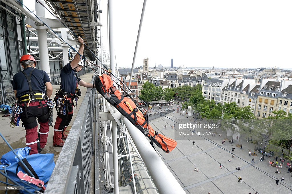 French firefighters from the GRIMP unit, specialized in vertical rescue operations, evacuate an injured from the top of the Centre Pompidou, contemporary art center, aka Beaubourg, in Paris, as they stage a drill on July 30, 2013. AFP PHOTO / MIGUEL MEDINA