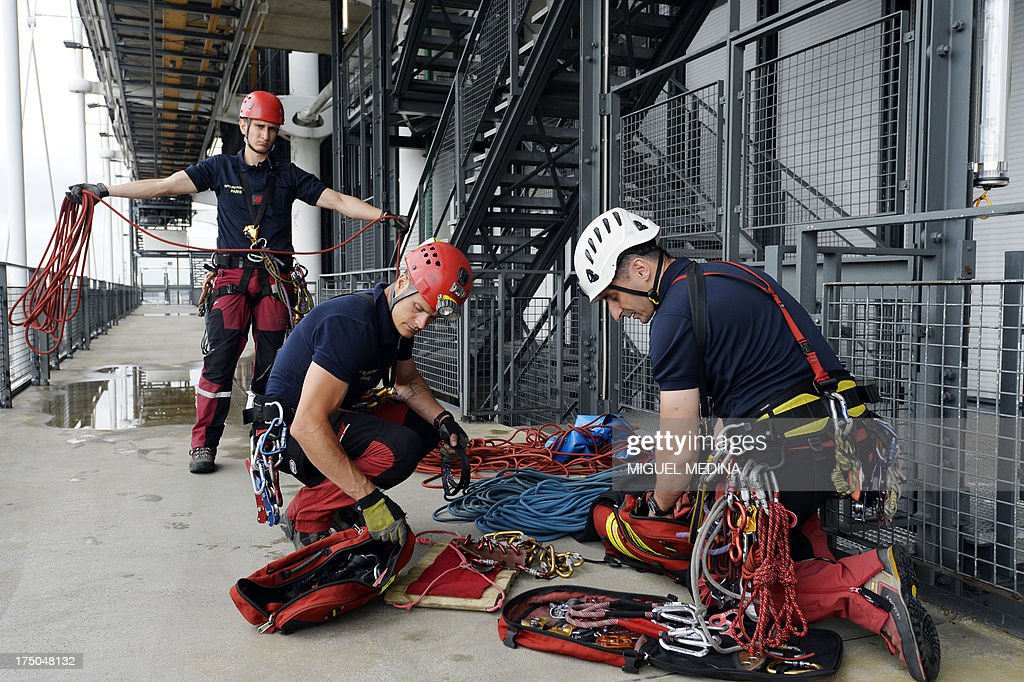 French firefighters from the GRIMP unit, specialized in vertical rescue operations, prepare climbing ropes as they stage a drill on July 30, 2013 at the Centre Pompidou, contemporary art center, aka Beaubourg, in Paris.