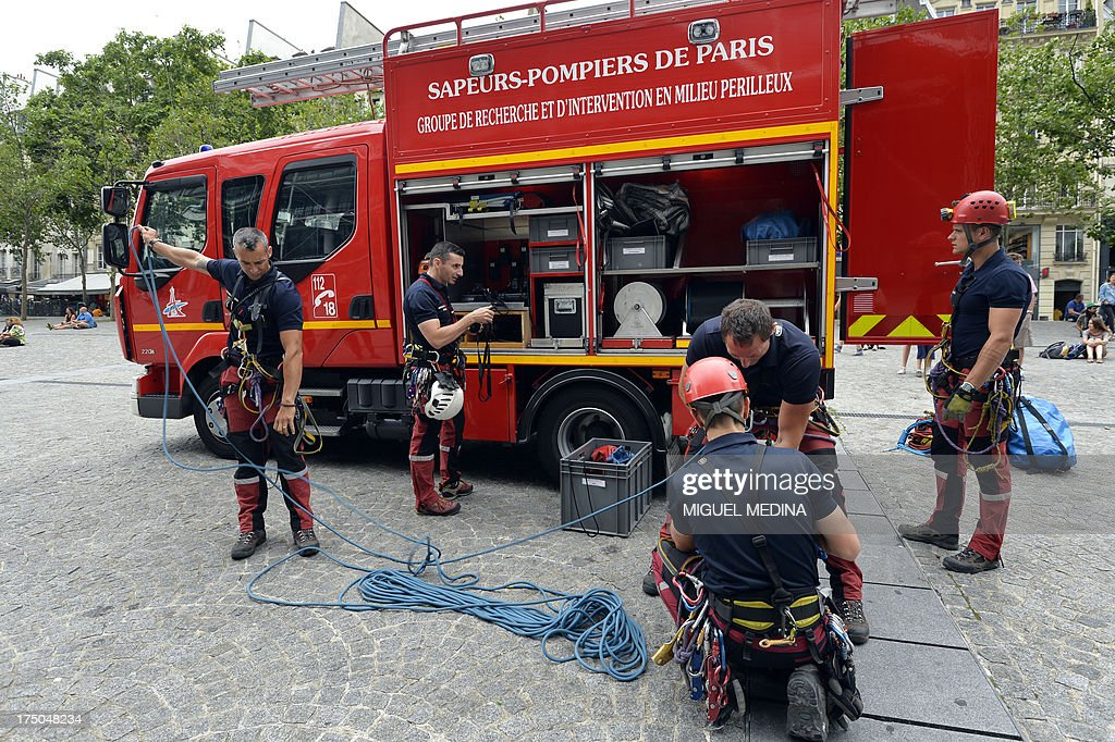 French firefighters from the GRIMP unit, specialized in vertical rescue operations, prepare climbing ropes to stage a drill on July 30, 2013 at the Centre Pompidou, contemporary art center, aka Beaubourg, in Paris.