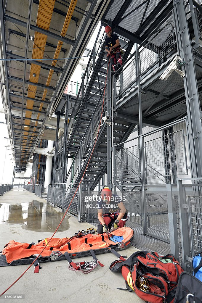 French firefighters from the GRIMP unit, specialized in vertical rescue operations, prepare to evacuate an injured as they stage a drill on July 30, 2013 at the Centre Pompidou, contemporary art center, aka Beaubourg, in Paris.