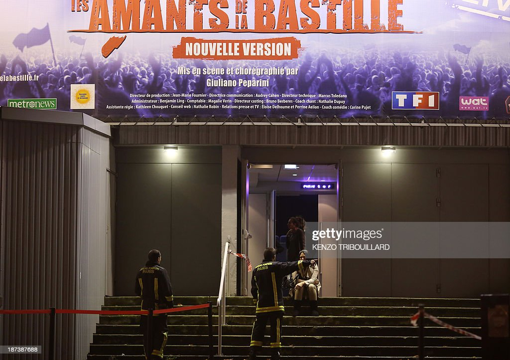 French firefighters speak with a woman sitting under a billboard of the musical '1789, The Lovers of Bastille' at the Palace of Sports at the Porte de Versailles in Paris following a blast on November 8, 2013. At least seven people were injured when an accidental explosion took place during a rehearsal of the play.
