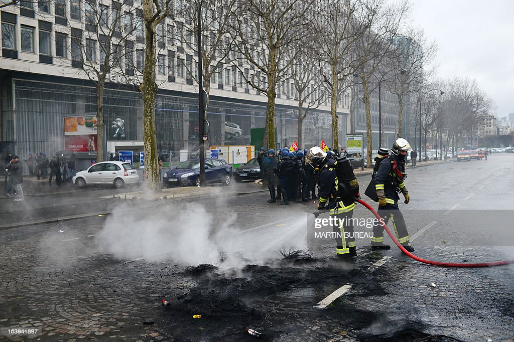 French firefighters spray water in a street near anti-riot policemen (background) on March 18, 2013 outside French auto giant PSA Peugeot Citroen's headquarters in Paris, after employees of PSA Aulnay plant protested with flares and burned tyres, while an extraordinary central works council was held to present the group's restructuring plans to trade union representatives. This extraordianry council was focused upon the closure by 2014 of the group's plant in Aulnay-sous-Bois, currently providing 2,800 jobs, and upon the 1,400 jobcuts planned in its plant in Rennes.