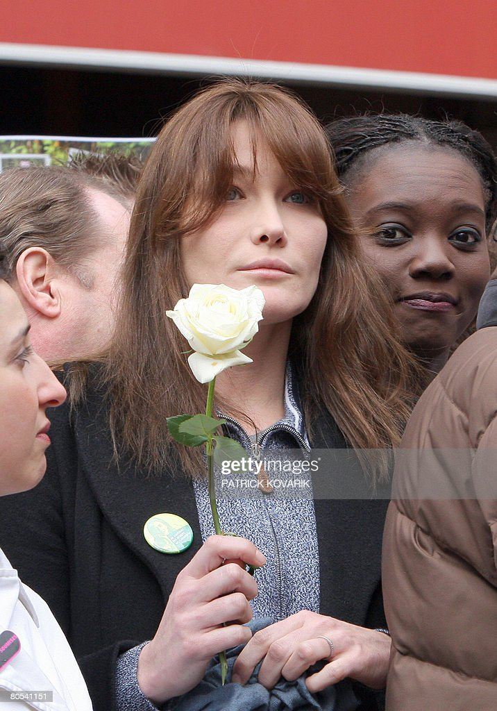 French first lady Carla BruniSarkozy holds up a white rose next to France's human rights deputy minister Rama Yade on April 6 2008 in Paris at the...
