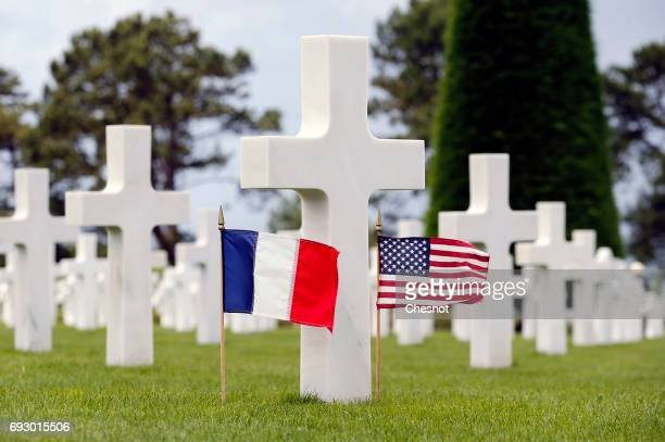 French flag and an US flag sit on the grave of a soldier during commemorations marking the 73th anniversary of DDay the June 61944 landings of Allied...
