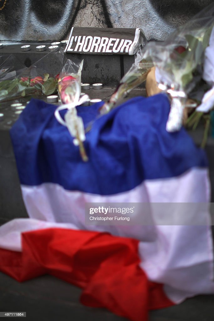 A French flag and flowers are are placed in tribute at Place de la Republique, the day after a deadly terrorist attack on November 14, 2015 in Paris, France. At least 120 people have been killed and over 200 injured, 80 of which seriously, following a series of terrorist attacks in the French capital.