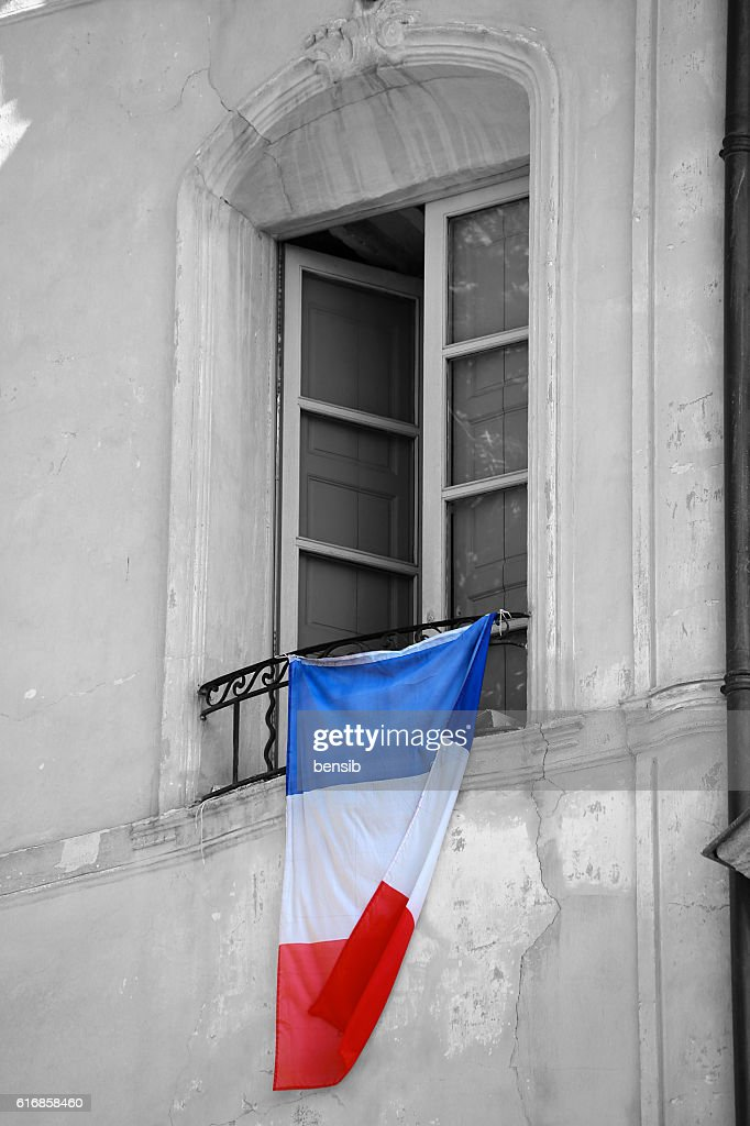 French Flag Hanging on the Window of a Building : Stock Photo