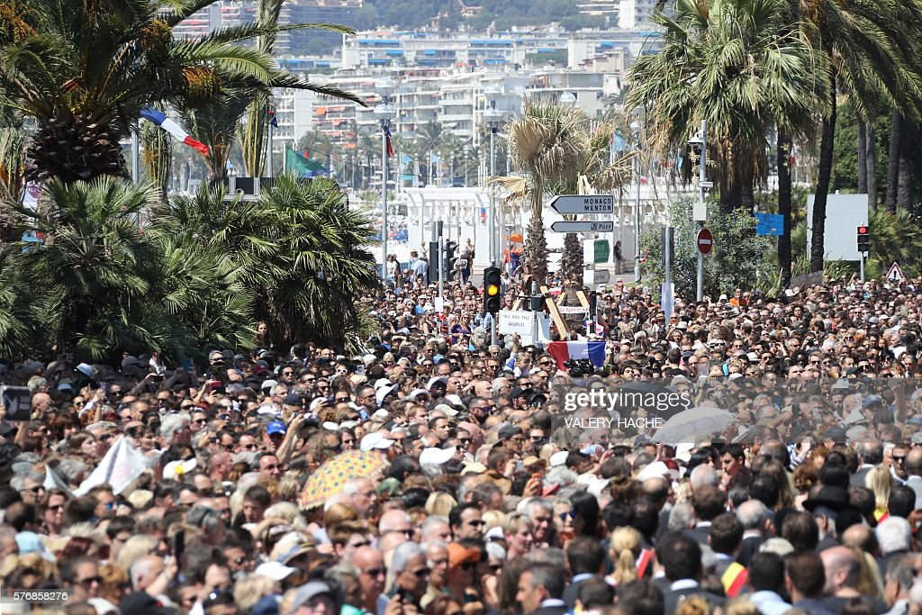A French flag is seen as people gather to observe a minute's silence at the Jardin Albert 1er on the Promenade des Anglais seafront in Nice, on July 18, 2016, in tribute to the victims of the deadly Nice attack on Bastille day. France was set to hold a minute's silence on July 18, 2016 to honour the 84 victims of the Nice truck attack, but a period of national mourning was overshadowed by bickering politicians. Church bells will toll across the country, and the country will fall silent at midday, a now grimly familiar ritual after the third major terror attack in 18 months on French soil. / AFP / Valery HACHE