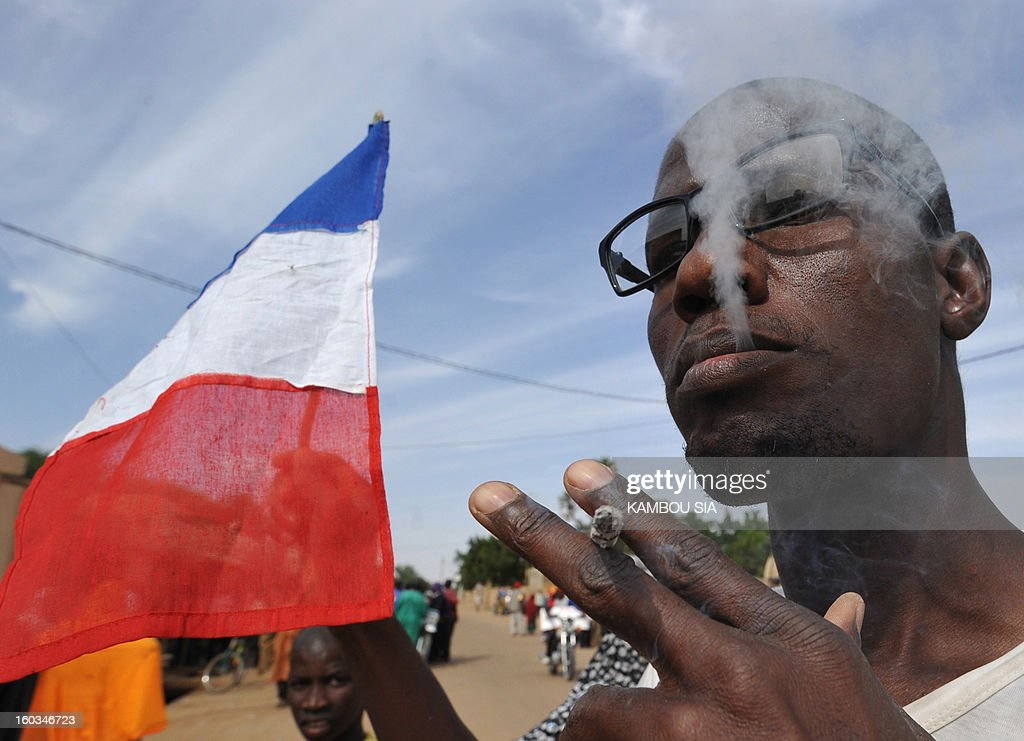 A French flag is seen next to a man enjoying a cigarette on January 29, 2013 in Ansongo, a town south of the northern Malian city of Gao, as Niger troops entered the city. Troops from Niger and Mali on January 29 entered Ansongo, which along with Gao was recaptured by French-led soldiers over the weekend in a lightning offensive against radicals holding Mali's north. So far, just 2,000 African troops have been sent to Mali or neighboring Niger, many of them from Chad, to boost the French-led offensive which began on January 11 and led to the recapture of several towns, including Ansongo.