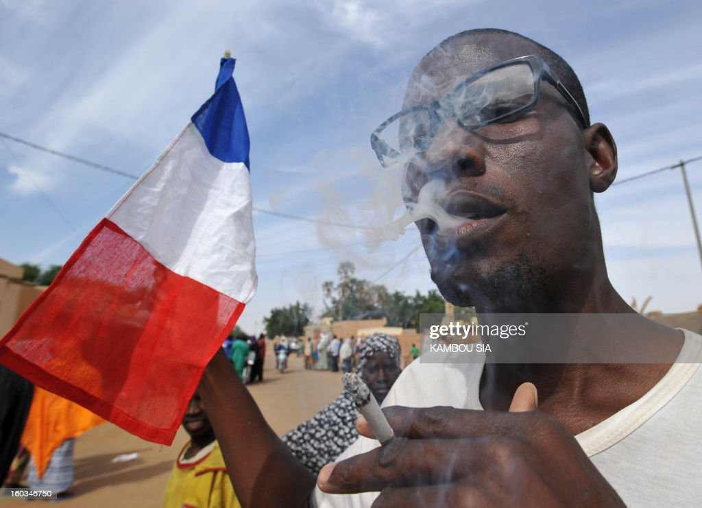 A French flag is seen next to a man enjoying a cigarette on January 29, 2013 in Ansongo, a town south of the northern Malian city of Gao, as Niger troops entered the city. Troops from Niger and Mali on January 29 entered Ansongo, which along with Gao was recaptured by French-led soldiers over the weekend in a lightning offensive against radicals holding Mali's north. So far, just 2,000 African troops have been sent to Mali or neighboring Niger, many of them from Chad, to boost the French-led offensive which began on January 11 and led to the recapture of several towns, including Ansongo. AFP PHOTO / KAMBOU SIA