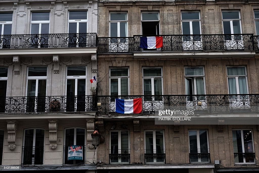 French flags are seen hanging from the balconies of homes in the center of Lille prior to the Euro 2016 round of sixteen football match between Germany and Slovakia at the stadium 'Stade Pierre-Mauroy' in Lille, France on June 26, 2016 during the Euro 2016 football tournament. / AFP / PATRIK