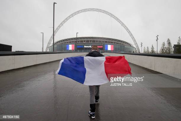 A French football fan draped in the national flag walks towards Wembley Stadium in west London on November 17 ahead of the international friendly...