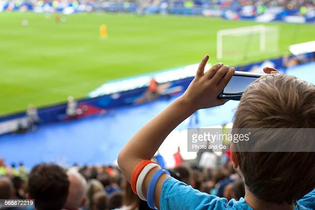 French football fan taking cell phone picture