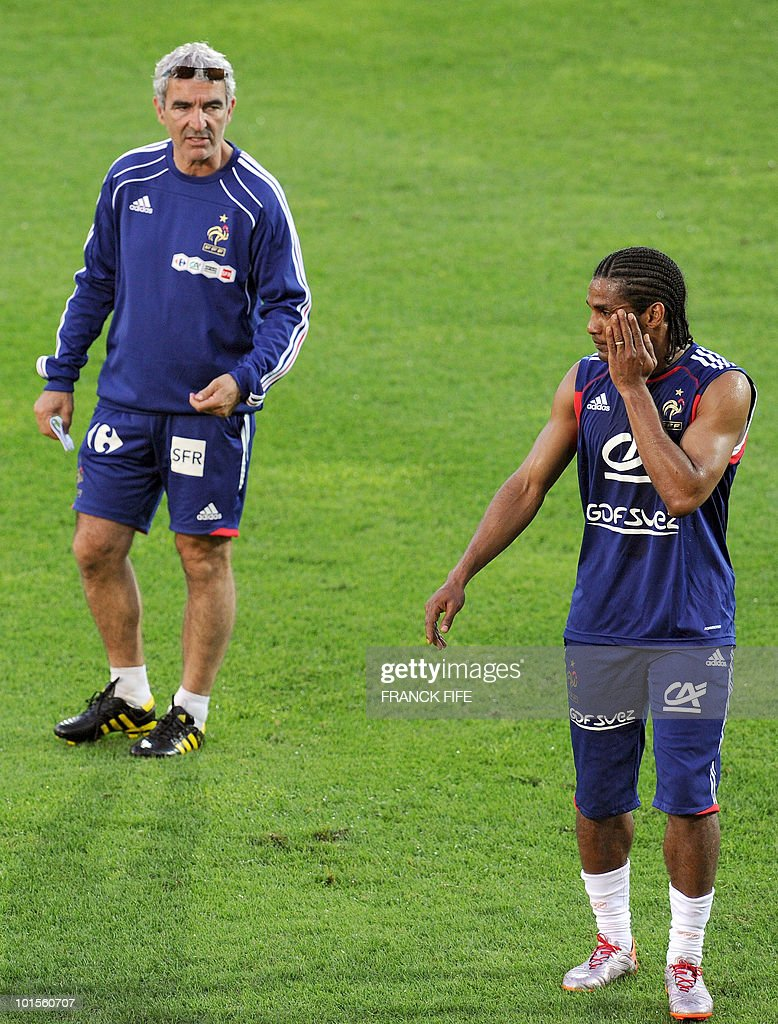 French football national team coach Raymond Domenech (L) speaks to midfielder Florent Malouda during the training session, on June 2, 2010 at the Michel Volnay stadium in Saint-Pierre, on the French Indian Ocean island of La Reunion, as part of the preparation for the upcoming World Cup 2010. France have one remaining friendly scheduled against China in Reunion on June 4, 2010. They open their World Cup campaign against Uruguay on June 11.