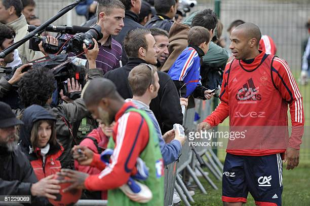 French football national team forward Thierry Henry talks with fans as other forward Djibrill Cisse signs autographs after a training session in...