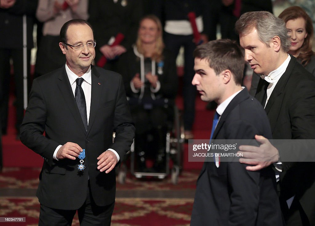 French football player and 2012 London Paralympic Games silver medalist David Labarre (2ndR) is about to receive from France's President Francois Hollande, the Knight Award in the National Order of Merit during a ceremony at the Elysee presidential Palace on February 22, 2013 in Paris.