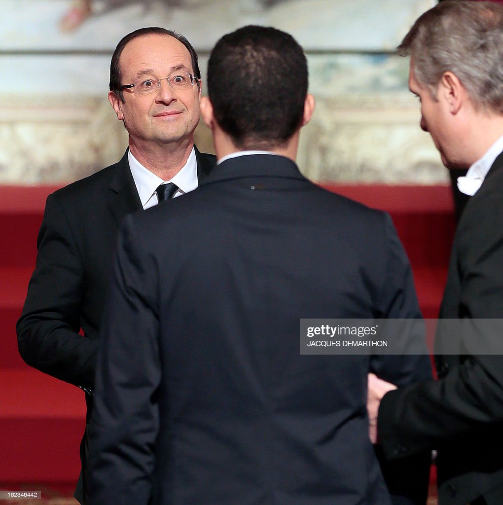 French football player and 2012 London Paralympic Games silver medalist Hakim Arezki receives the Knight Award in the National Order of Merit from France's President Francois Hollande (L) during an awards ceremony at the Elysee Palace on February 22, 2013 in Paris.