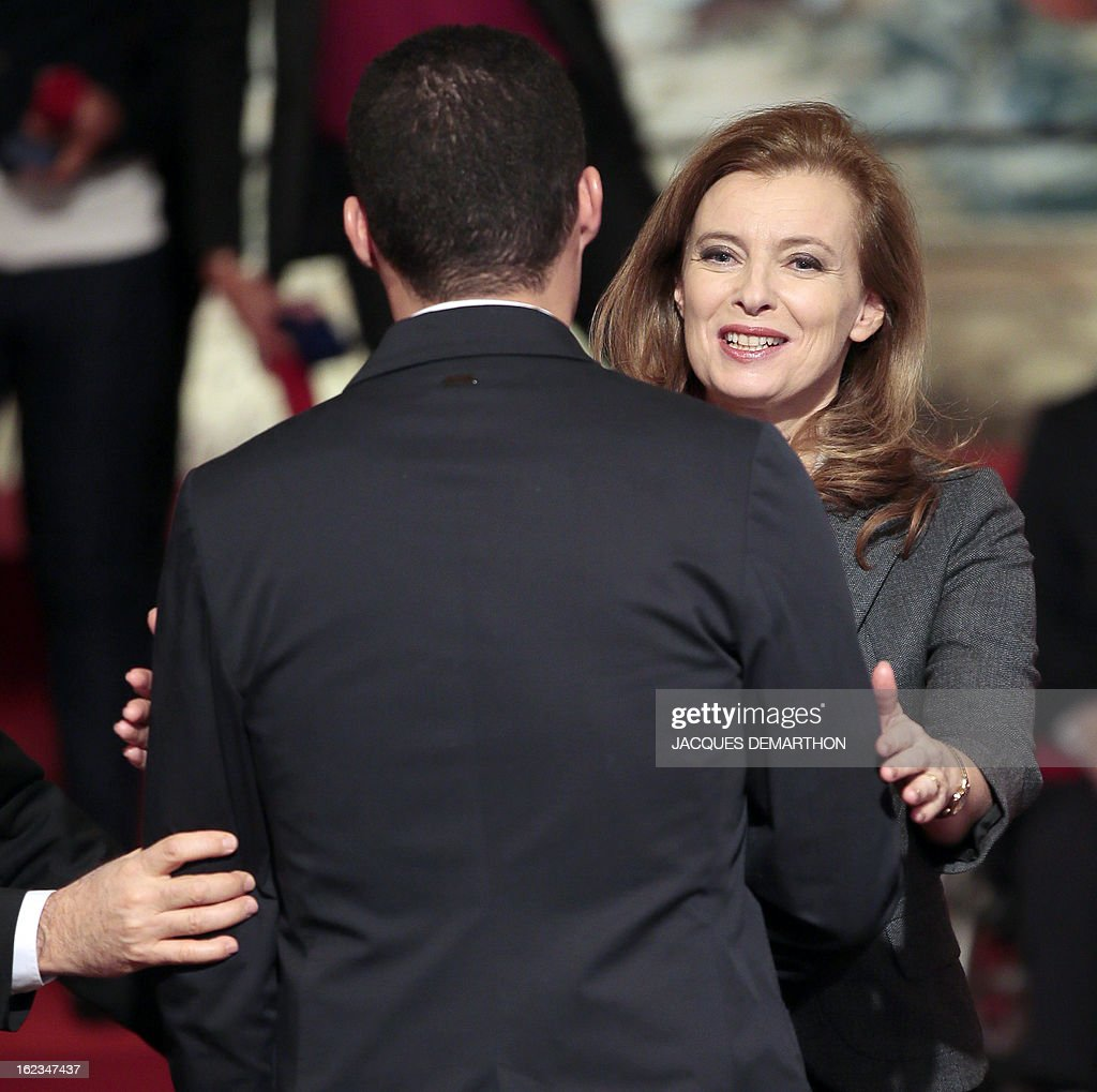 French football player and 2012 London Paralympic Games silver medalist Hakim Arezki (L) is congratulated by French President's companion Valerie Trierweiler after receiving the Knight Award in the National Order of Merit during a ceremony at the Elysee Palace on February 22, 2013 in Paris.