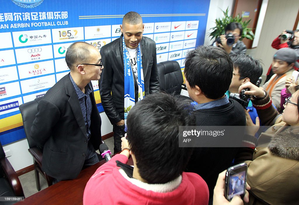 French football player Guillaume Hoarau (C) attends a press conference held by Dalian Aerbin club in Dalian, northeast China's Liaoning province on January 9, 2013. Hoarau has become the latest footballer to be enticed to the big spending Chinese Super League, siging a three year deal with Dalian Aerbin, the club announced on January. CHINA