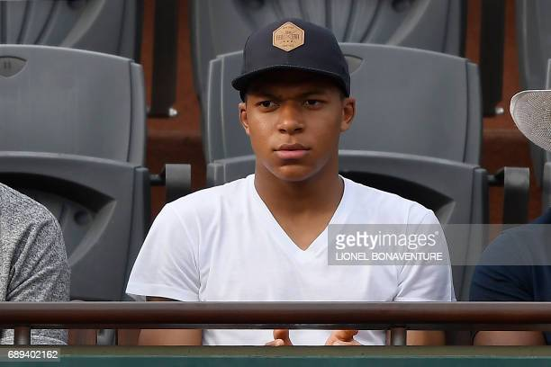 French football player Kylian Mbappe attends the tennis match between France's Lucas Pouille and France's Julien Benneteau at the Roland Garros 2017...
