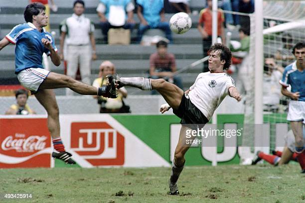 French football player Manuel Amoros fights for the ball with German opponent Lothar Matthäus during the World Cup football match between France and...