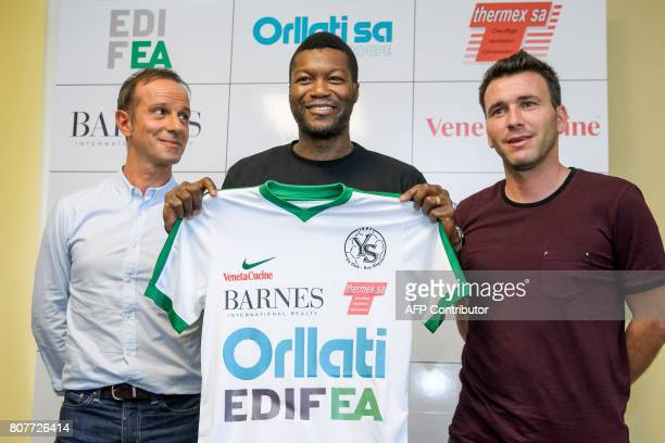French footballer Djibril Cisse poses with his new team jersey between Yverdon Sport FC president Mario Di Pietrantonio and team coach Anthony...