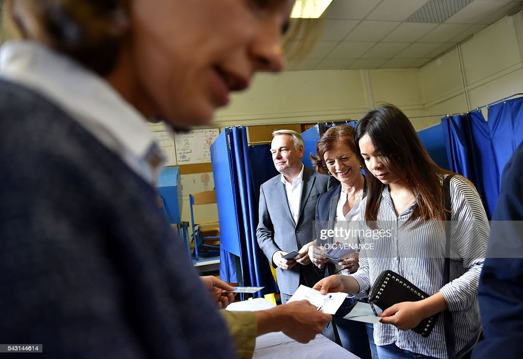 French Foreign Affairs minister and former mayor of Nantes Jean-Marc Ayrault (L) and his wife Brigitte (C) queue to cast their ballots on June 26, 2016, in Nantes during a local referendum organized in Loire Atlantique regarding the transfer of the Nantes Atlantique airport to Notre-Dame-des-Landes. Nearly One million people living in France's Loire-Atlantique department are voting in a referendum which poses the question 'Are you in favour of the project to transfer the Nantes-Atlantique airport to the municipality of de Notre-Dame-des-Landes?' to voters. The referendum was organised by the French executive power hoping to find a solution to the issue which has dragged on for 50 years.