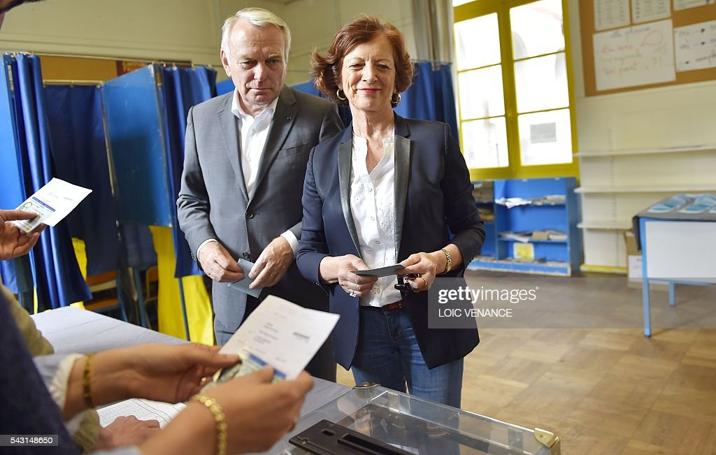 French Foreign Affairs minister and former mayor of Nantes Jean-Marc Ayrault (C) and his wife Brigitte wait to cast their ballots on June 26, 2016, in Nantes during a local referendum organised in Loire Atlantique regarding the transfer of the Nantes Atlantique airport to Notre-Dame-des-Landes. Nearly one million people living in France's Loire-Atlantique department are voting in a referendum which poses the question 'Are you in favour of the project to transfer the Nantes-Atlantique airport to the municipality of de Notre-Dame-des-Landes?' to voters. The referendum was organised by the French executive power hoping to find a solution to the issue which has dragged on for 50 years. / AFP / LOIC