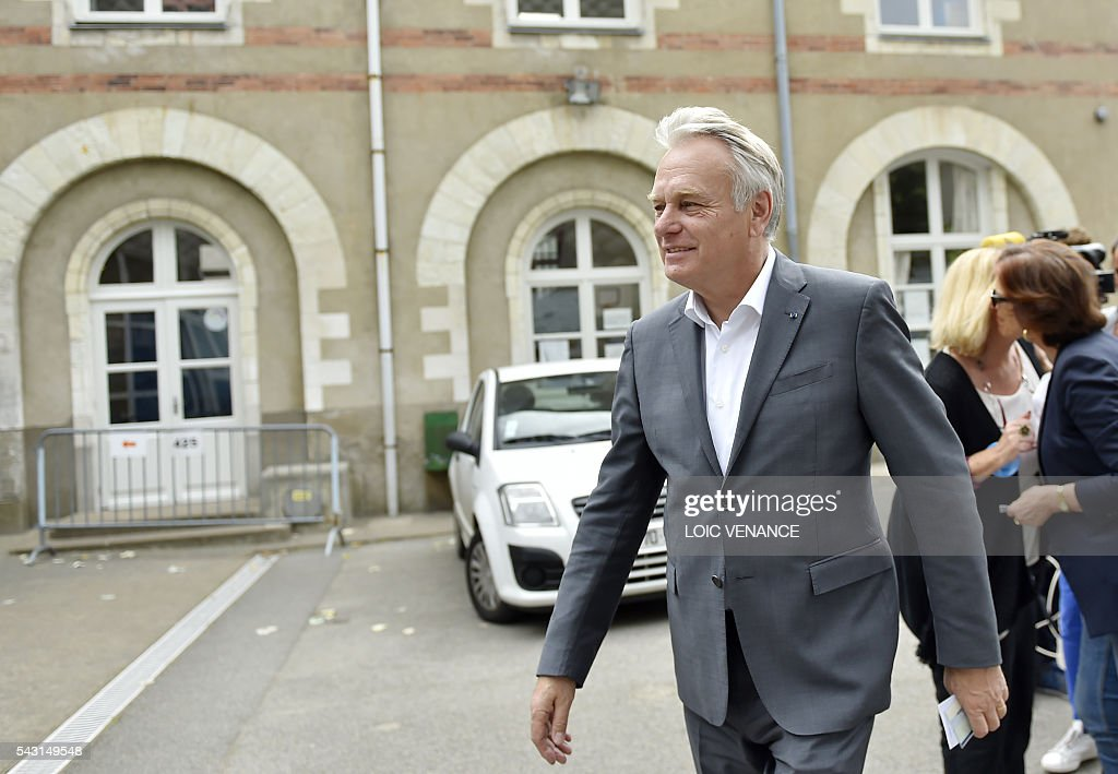 French Foreign Affairs minister and former mayor of Nantes Jean-Marc Ayrault (R) leaves after voting on June 26, 2016, in Nantes during a local referendum organised in Loire Atlantique regarding the transfer of the Nantes Atlantique airport to Notre-Dame-des-Landes. Nearly One million people living in France's Loire-Atlantique department are voting in a referendum which poses the question 'Are you in favour of the project to transfer the Nantes-Atlantique airport to the municipality of de Notre-Dame-des-Landes?' to voters. The referendum was organised by the French executive power hoping to find a solution to the issue which has dragged on for 50 years. / AFP / LOIC