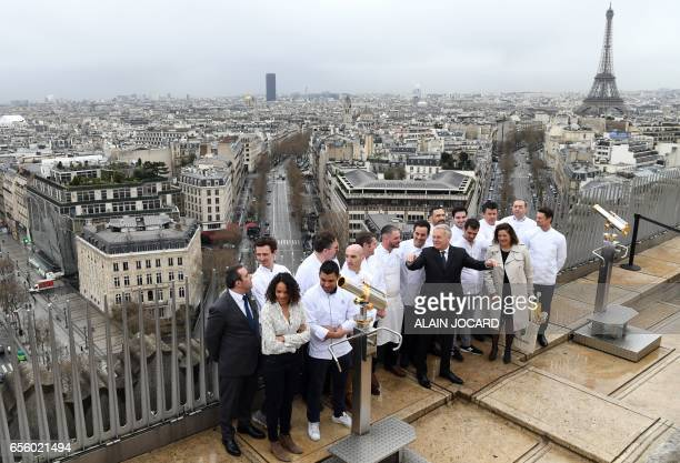 French Foreign Affairs minister JeanMarc Ayrault gestures as he poses for a picture with French chefs on top of the Arc de Triomphe as the Eiffel...