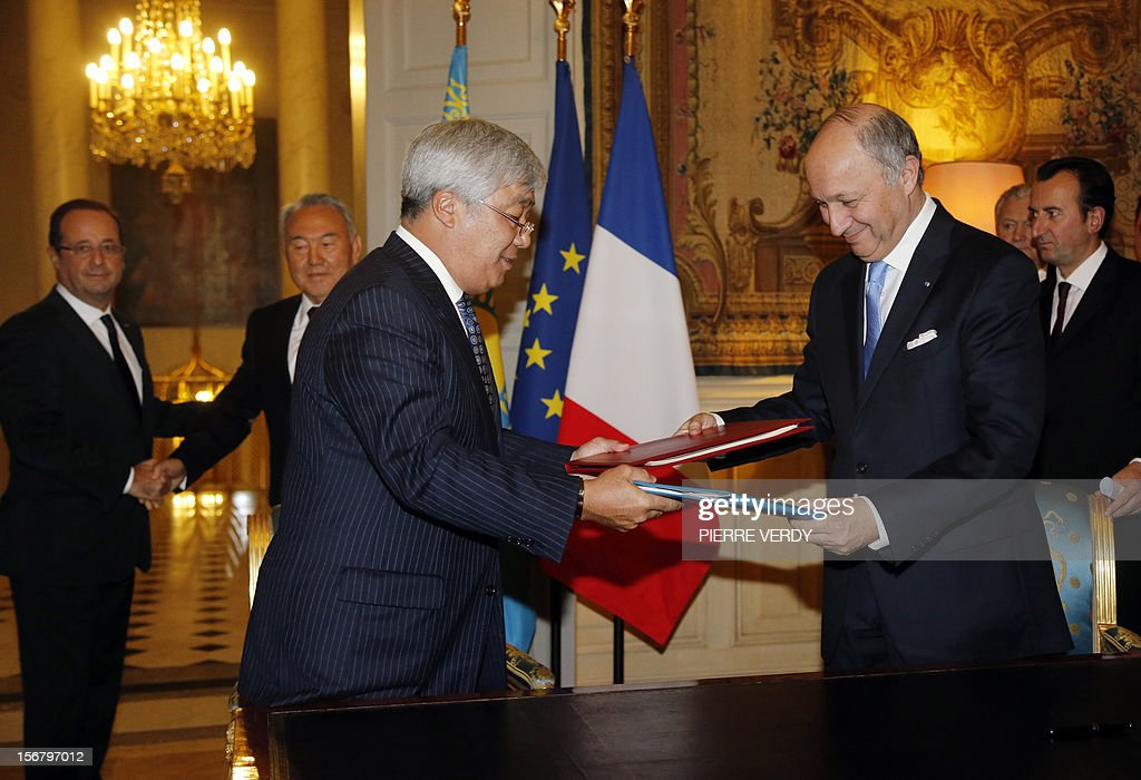 French Foreign Affairs minister Laurent Fabius (R) and his Kazakh counterpart Erlan A. Idrissov (C) exchange a military agreement focused on the French troops in Afghanistan, as France's President Francois Hollande (L) and Kazakhstan's President Nursultan Nazarbayev (2ndL) look on, on November 21, 2012 at the Elysee Palace in Paris. POOL AFP PHOTO PIERRE VERDY