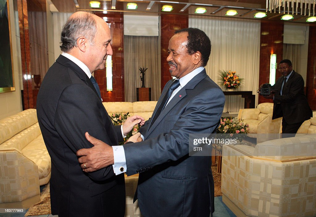 French foreign affairs minister Laurent Fabius (L) shakes hands with Cameroonian President Paul Biya on March 15, 2013 in Yaounde. Visiting Cameroon, Fabius spoke to Biya about the kidnapping of a French family of seven, including four children, from a nature park in Cameroon near the Nigerian border, which occured on February 19, 2013. Fabius, who will go to Nigeria on Saturday, has also come to discuss the French military intervention in Mali. AFP PHOTO/STR