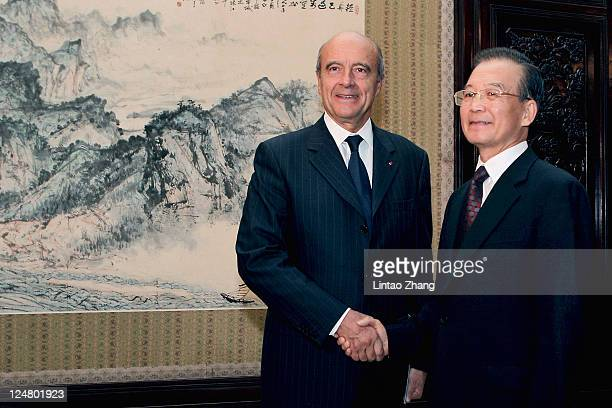 French Foreign Minister Alain Juppe shakes hands with Chinese Premier Wen Jiabao during their meeting at the Zhongnanhai leaders' compound on...