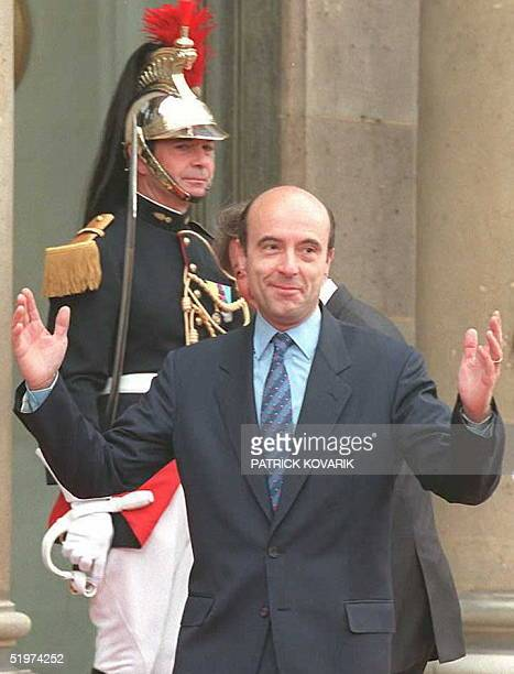French Foreign Minister Alain JuppT waves to photographers 17 May as he arrives at the Elysee Palace to attend the handover of presidential powers...