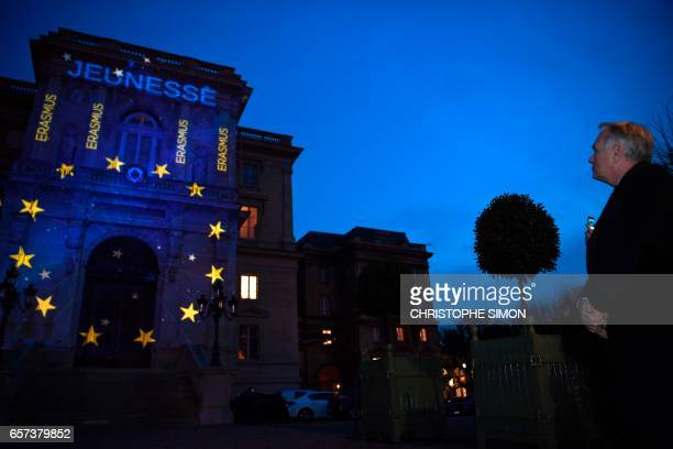 French Foreign Minister JeanMarc Ayrault watches the word Equality and the logo of the Europen Union projected during a light show onto the French...