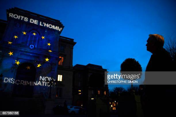 French Foreign Minister JeanMarc Ayrault watches the words Human Rights and the logo of the Europen Union projected during a light show onto the...