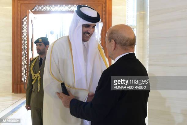 French Foreign Minister JeanYves Le Drian shakes hands with Qatari Emir Sheikh Tamim bin Hamad alThani during a meeting in Doha on December 7 2017 /...
